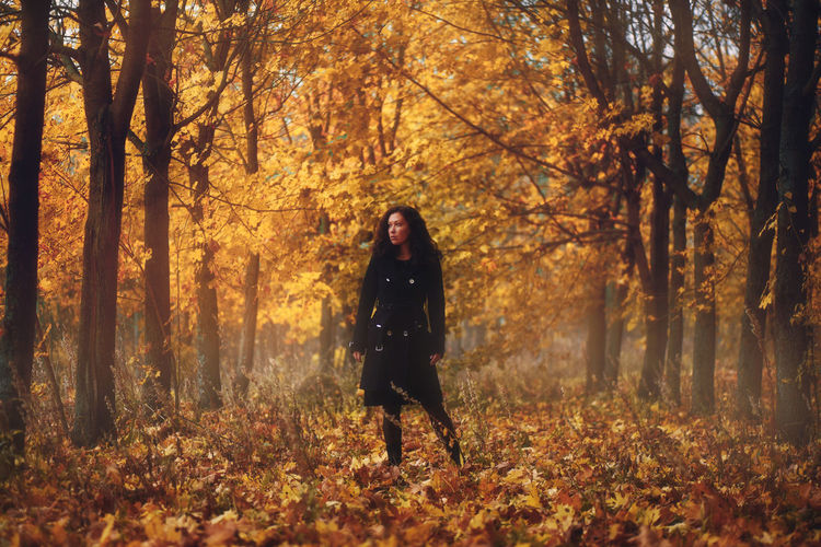 Full length of woman standing in forest during autumn
