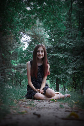 Portrait of young woman sitting on ground against trees in forest