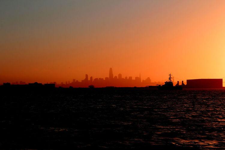 Silhouette buildings by sea against orange sky