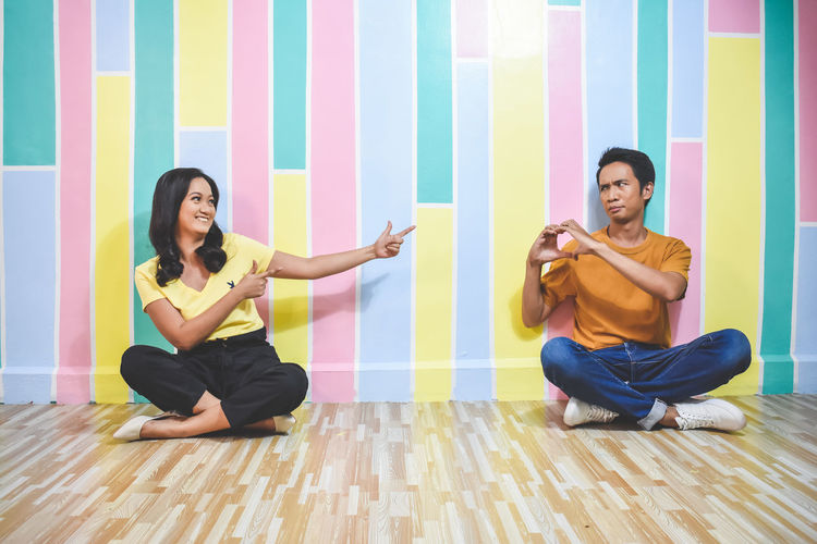 Young couple sitting on floor against wall
