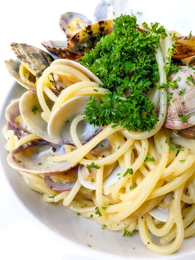 Close-up of noodles served with clams in plate
