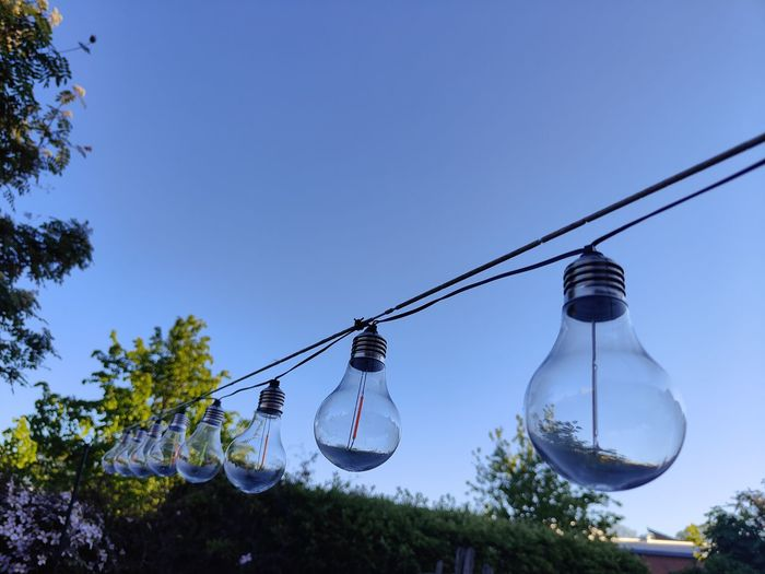 Low angle view of light bulbs hanging against clear blue sky