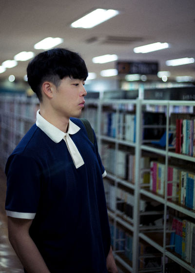 Side view of young man standing in library