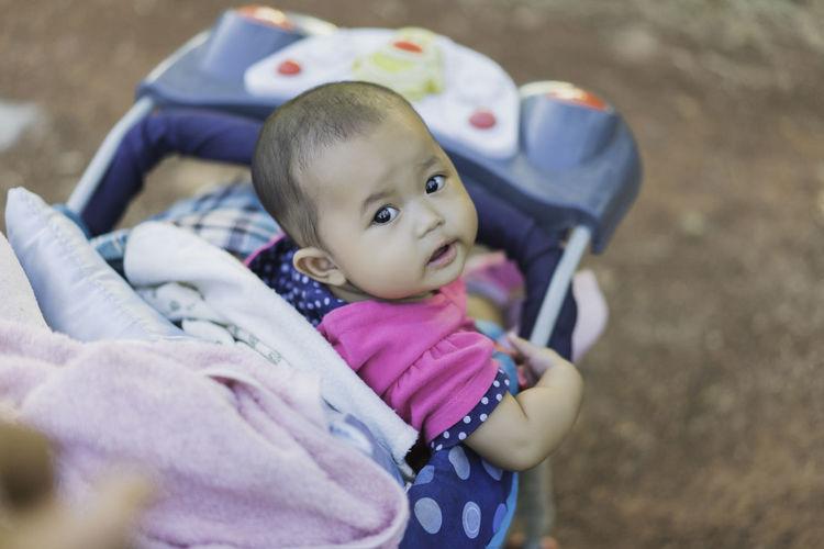 Portrait of baby girl sitting in stroller