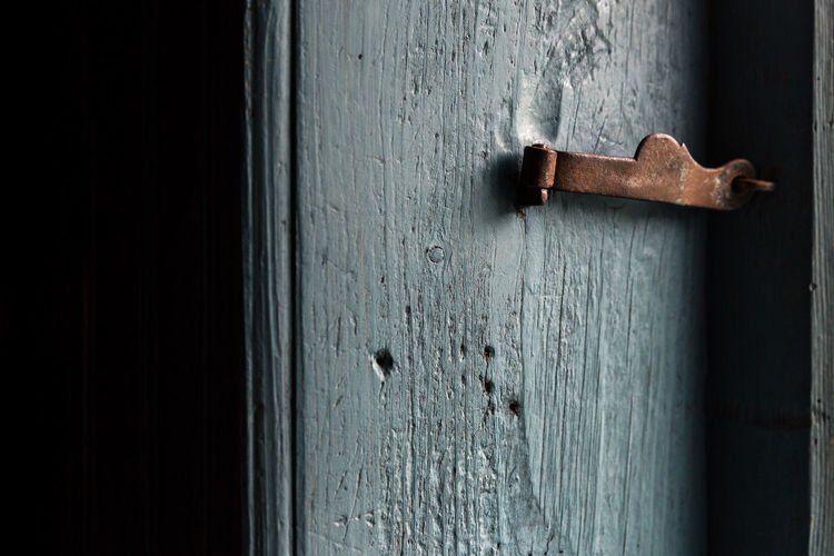 Close-Up Of Latch On Wooden Door In Darkroom