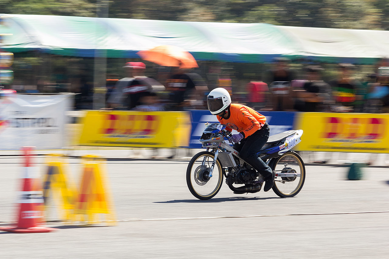 blurred motion, motion, transportation, real people, mode of transportation, speed, city, men, lifestyles, people, group of people, street, sport, road, land vehicle, incidental people, competition, motorcycle, riding, ride