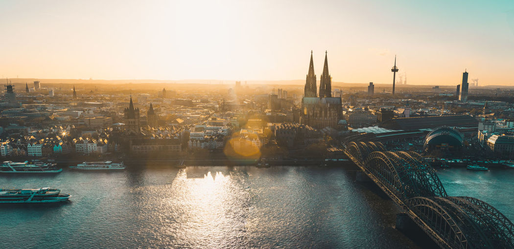 Panoramic view of Cologne, Germany, with Cologne Cathedral, Hohenzollern Bridge and old town at sunset Cologne Cologne Cathedral Cityscape Skyline Köln Kölner Dom Tourist Attraction  Tourist Destination Europe Germany Rhine Rhine River Hohenzollernbrücke Hohenzollernbridge Old Town Sunset Church Gothic Architecture