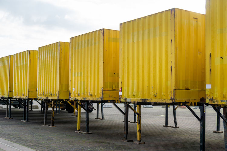 Yellow metallic structure on pier by building against sky