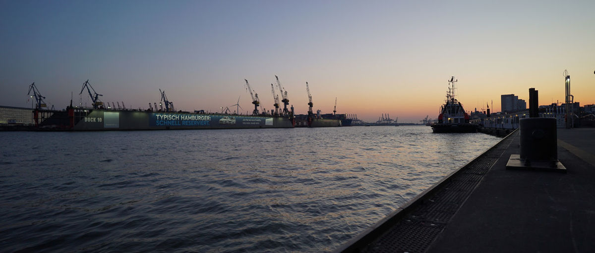 Commercial dock by sea against clear sky during sunset