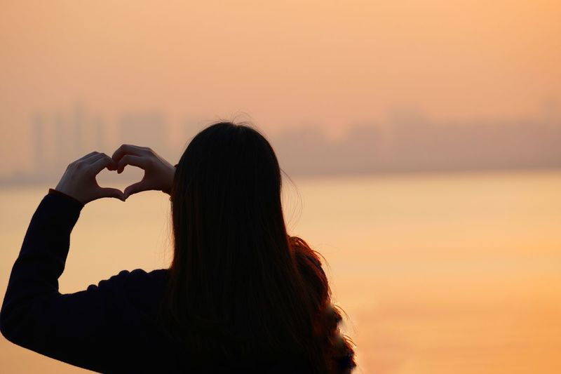 Rear view of woman making heart shape against sea during sunset