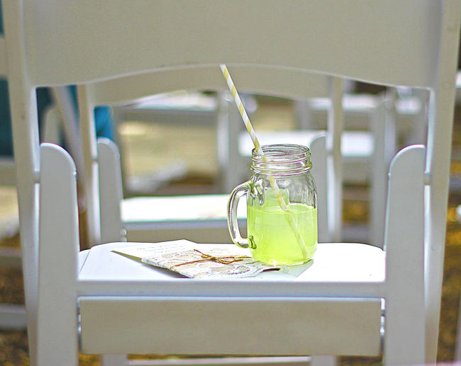 Close-up of juice in jar on chair