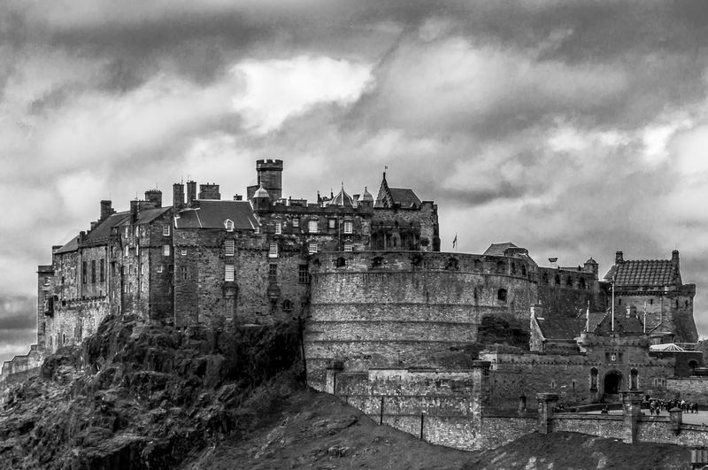 Low angle view of old edinburgh castle against cloudy sky