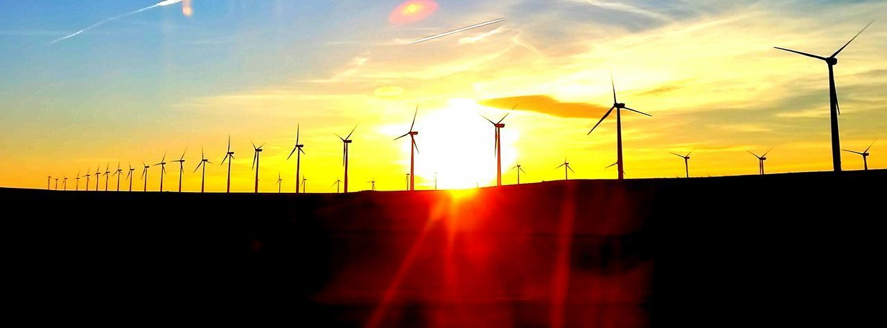 fuel and power generation, alternative energy, wind power, wind turbine, renewable energy, environmental conservation, sunset, windmill, sun, technology, orange color, sunlight, no people, industrial windmill, silhouette, sunbeam, sky, nature, beauty in nature, electricity, scenics, sustainable resources, outdoors, traditional windmill, day