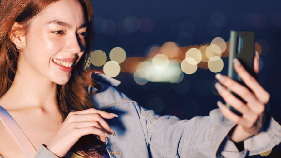 Portrait of woman using mobile phone at night
