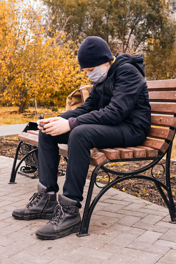 Man sitting on bench in park during autumn