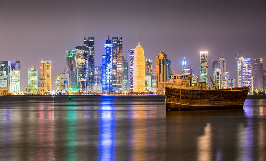 The skyline of Doha by night, Qatar Architecture Boat Building Exterior Built Structure City Cityscape Dhow Doha Illuminated Modern Nautical Vessel Night Nightphotography Qatar Reflection Reflection Sea Sky Skyscraper Travel Destinations Urban Skyline Water Waterfront