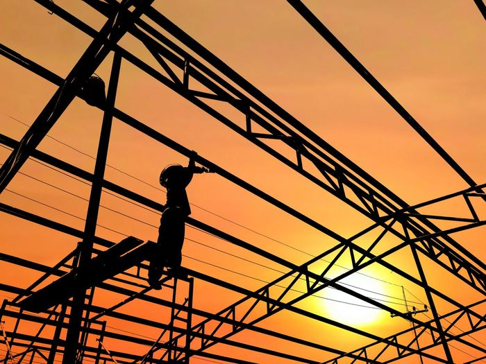 Low Angle View Of Silhouette Worker Standing On Electric Poles Against Sky During Sunset