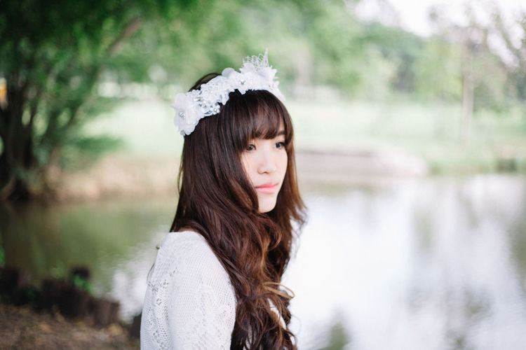 Beauty in white dress One Person Long Hair Portrait Young Adult Focus On Foreground Headshot Brown Hair Hairstyle Women Adult Beauty Hair Beautiful Woman Contemplation Tree Day Emotion Nature Outdoors Bangs Depression - Sadness