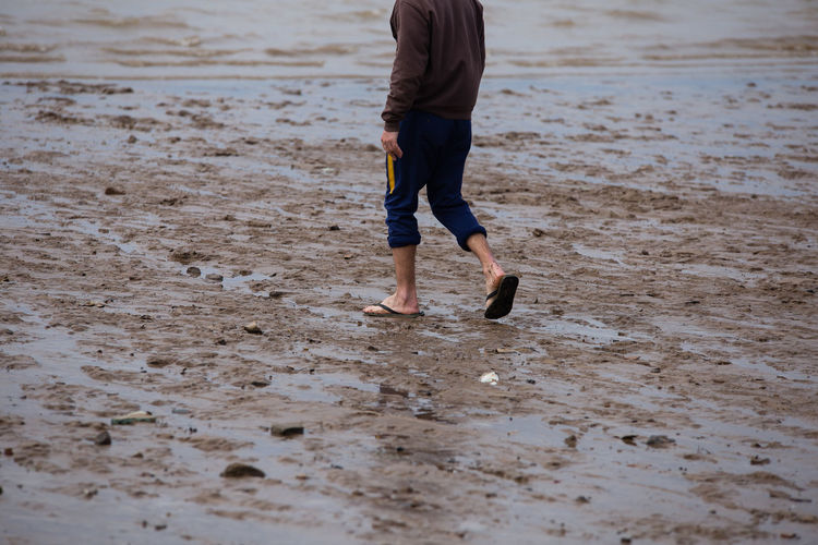 Beach Body Part Day Human Body Part Human Leg Land Leisure Activity Lifestyles Low Section Motion Mud Nature One Person Outdoors Real People Running Sand Sea Shorts Walking Water Wet