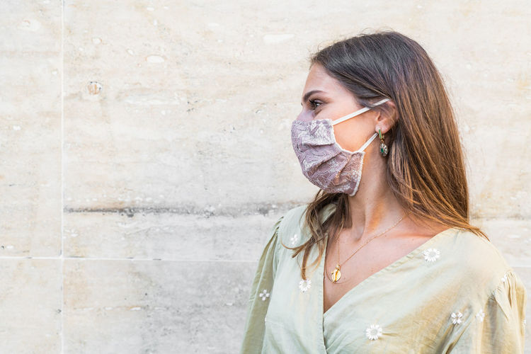 Smiling young woman wearing mask standing against wall outdoors