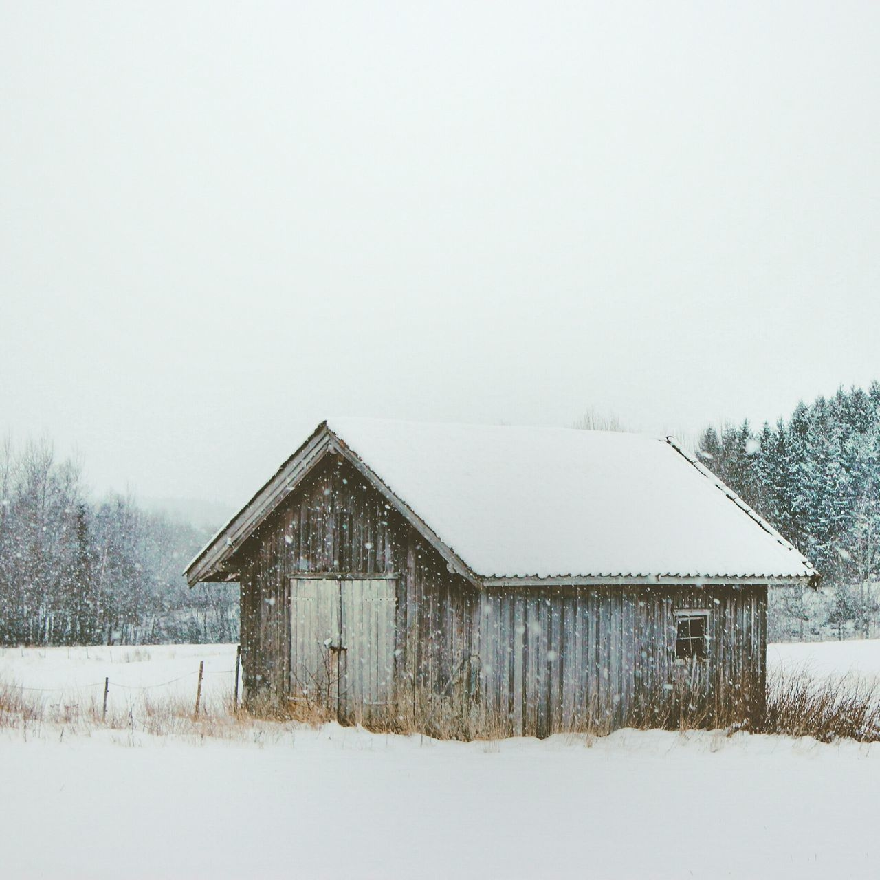 Barn Covered With Snow Against Clear Sky