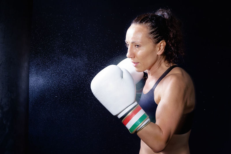 Woman practicing boxing against black background