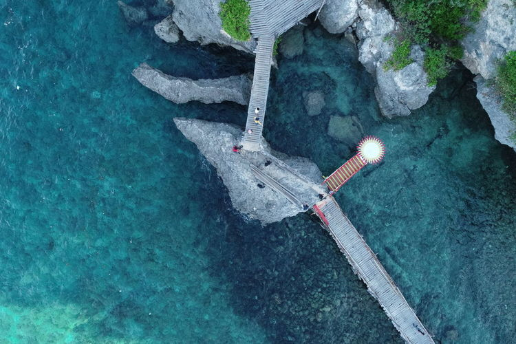 High angle view of umbrella on rock by sea