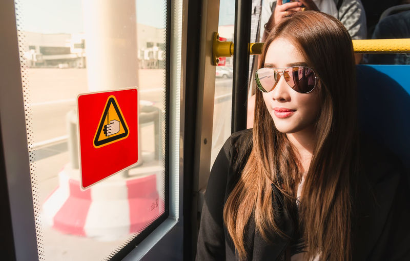 Woman wearing sunglasses while sitting by window in bus