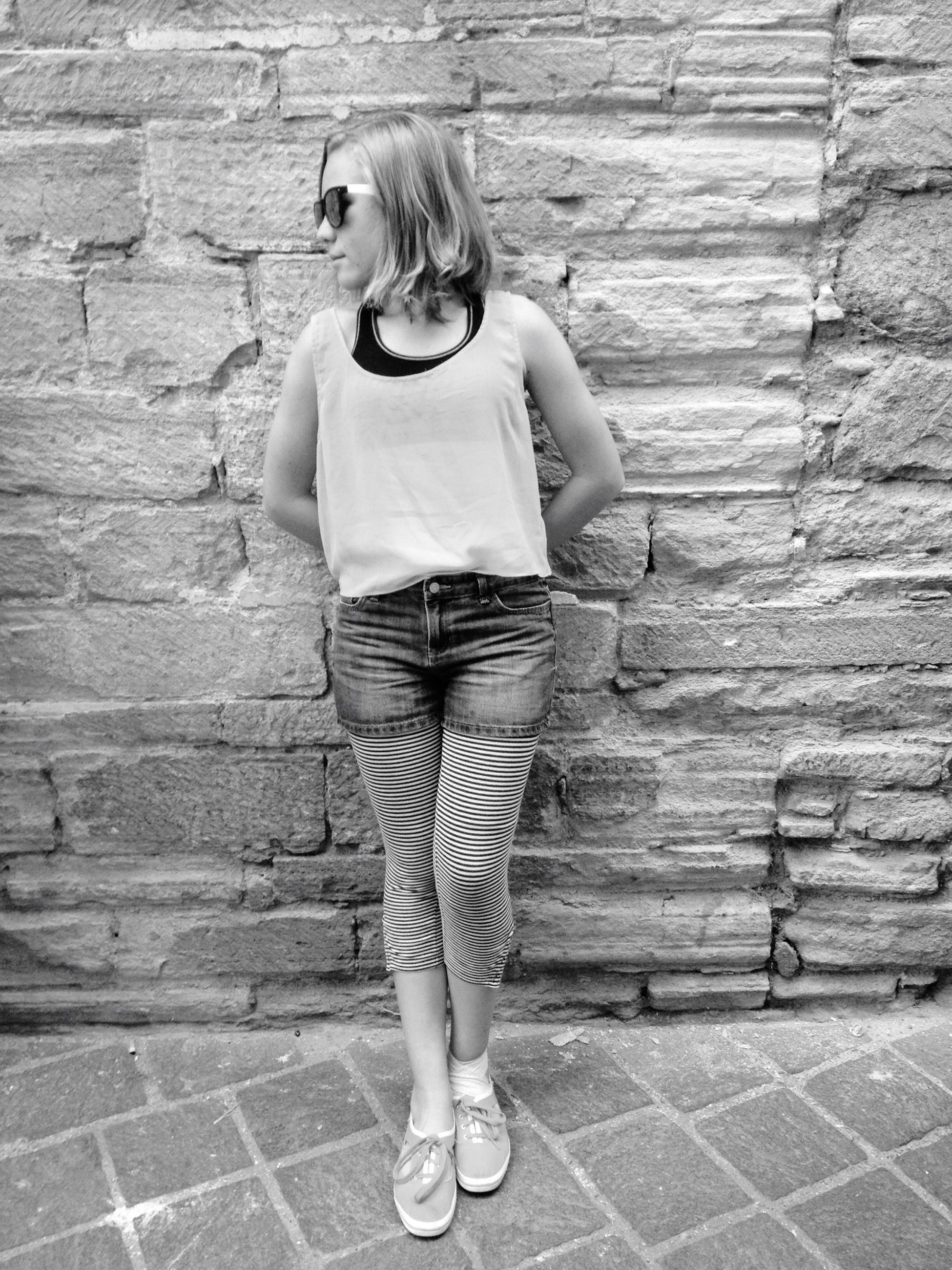 lifestyles, casual clothing, full length, leisure activity, standing, young adult, person, young women, front view, brick wall, wall - building feature, sidewalk, long hair, portrait, looking at camera, outdoors, day