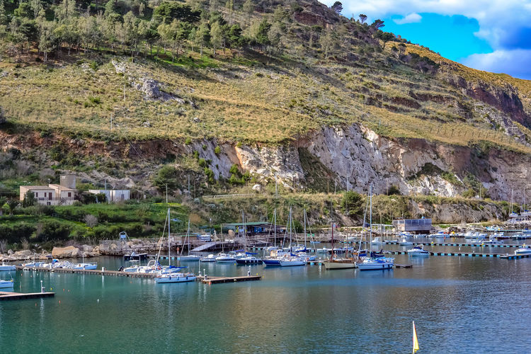 Sailboats moored on sea against mountain