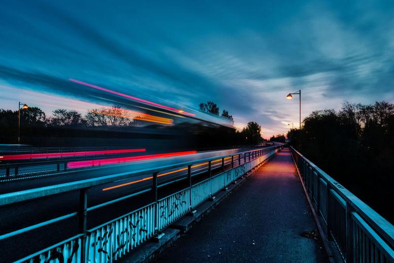 Blurred motion train against sky at dusk