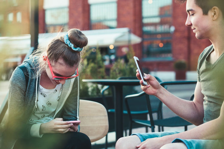Smiling teenage friends using mobile phone in city