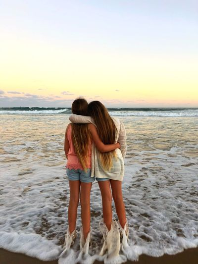 Rear view of friends with arms around standing at beach against sky during sunset