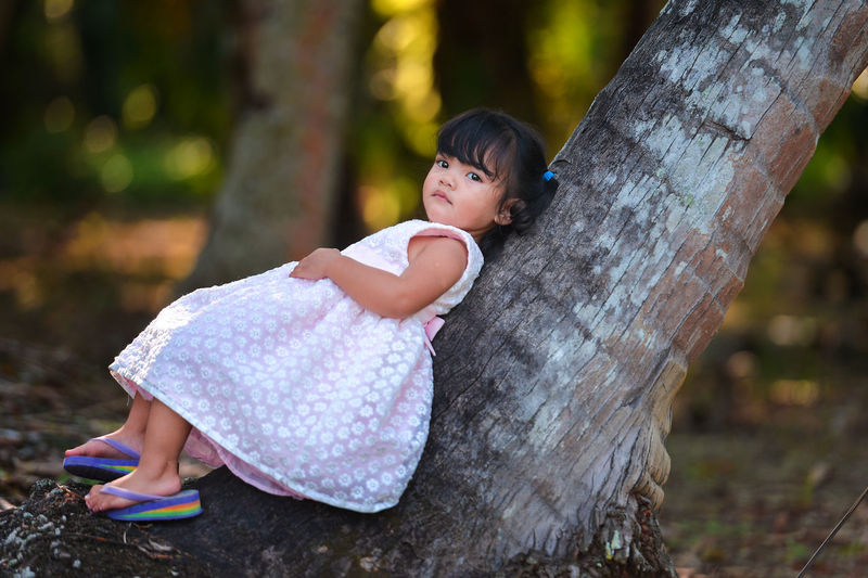 A unhappy child is lie down on coconut tree. Childhood Child One Person Tree Full Length Focus On Foreground Day Real People Cute Outdoors Nature Lifestyles