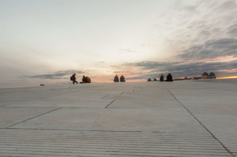 People relaxing on rooftop against sky during sunset