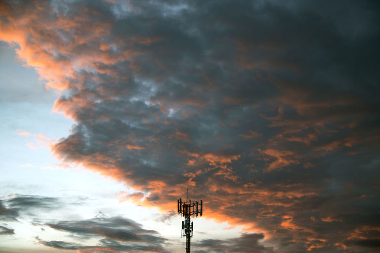 Low angle view of tower against dramatic sky during sunset