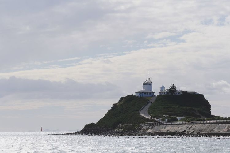 Lighthouse in sea against cloudy sky