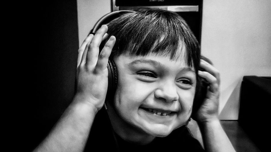 Close-up of smiling boy listening music at home