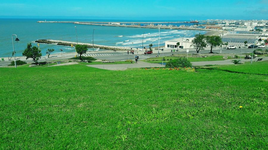 Grass Sea Beach Water Nature Green Color Beauty In Nature Outdoors Day Scenics Sand Horizon Over Water Vacations Sky No People Mar Del Plata Argentina Mardelplataarg Mardel Beauty In Nature Portrait Travel Destinations Building Exterior Architecture Built Structure Mardelplata