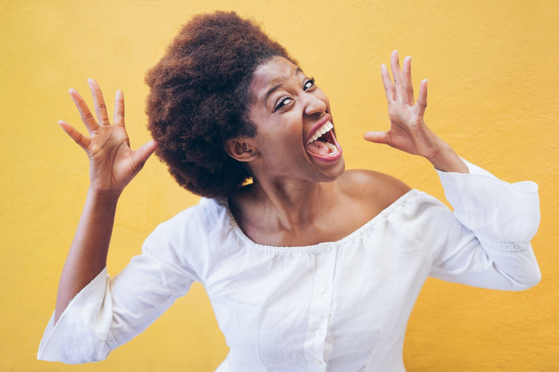 Screaming african woman with yellow background - Black crazy girl having fun in front of smartphone camera - Focus on eyes - Youth, fashion, lifestyle and trends concept Mouth Mouth Open Emotion One Person Casual Clothing Young Adult Yellow Gesturing Women Young Women Portrait Hairstyle Adult Hair Africa African Crazy WOW