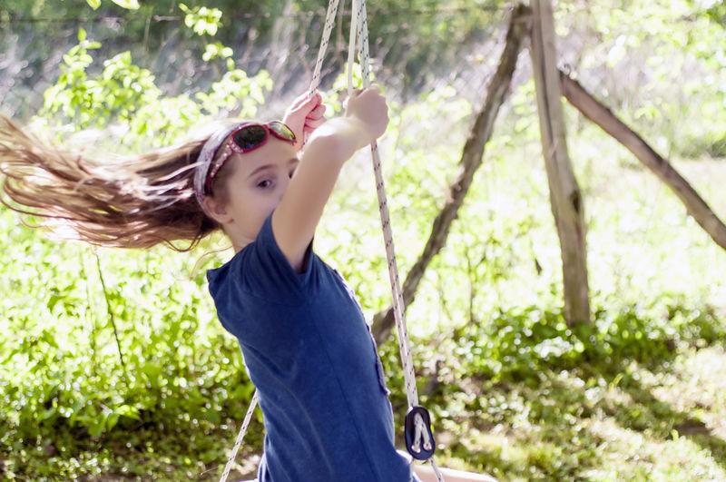 Portrait of girl sitting on swing against trees