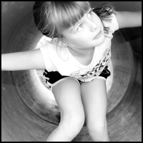 Girl crawling through a tunnel in black and white looking upwards Black And White Blackandwhite Looking Up At The Sky Looking Up Crawling Tunnel Little Girl Girl