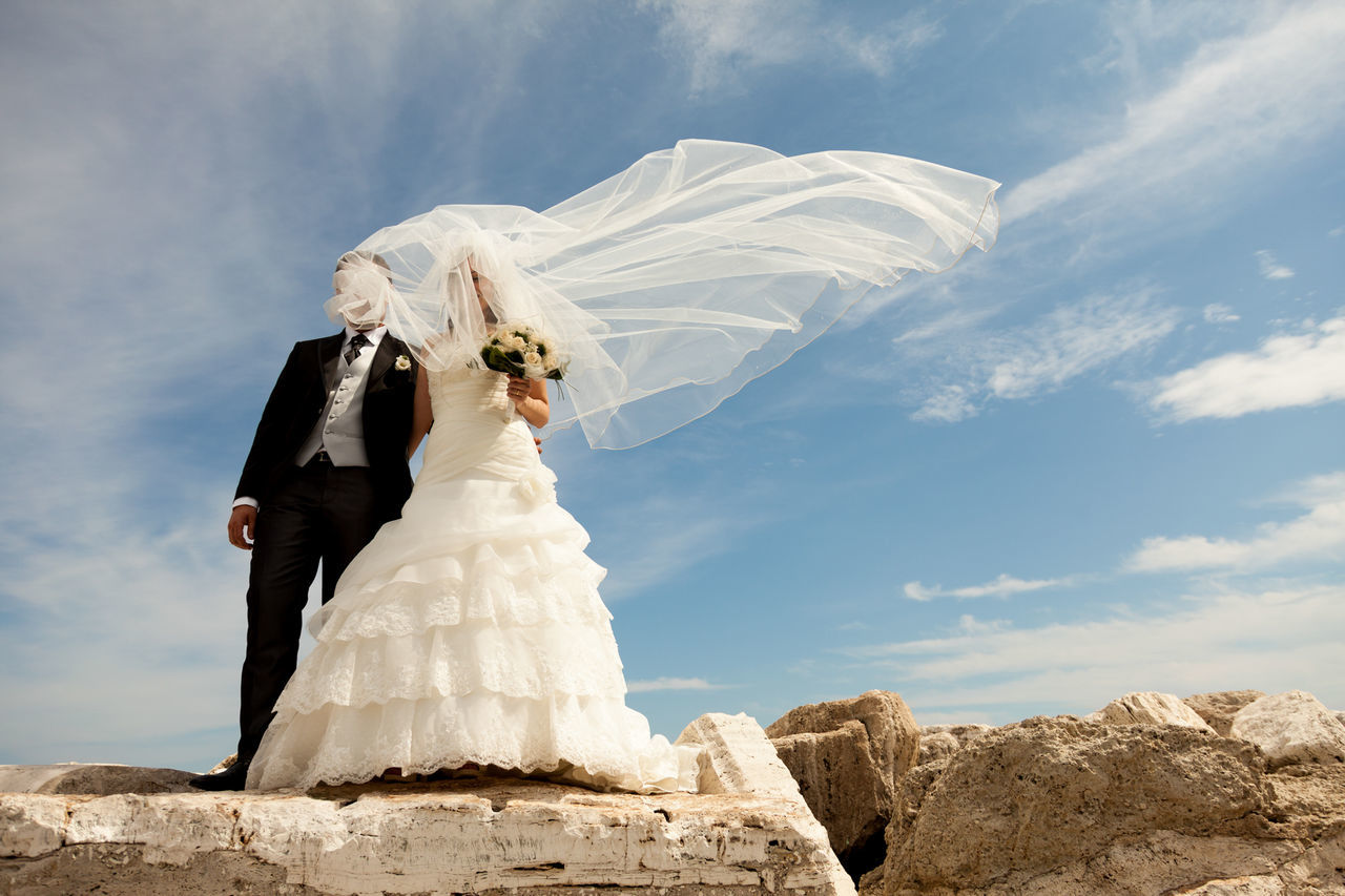 Low angle view of bride and groom standing on rocks against sky