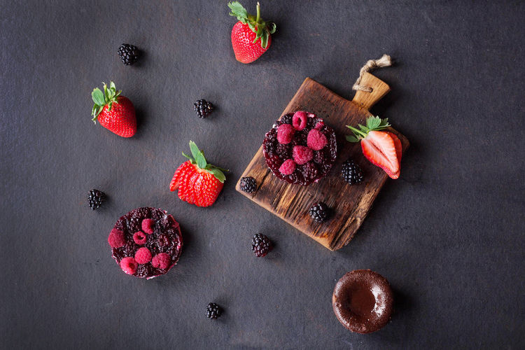 High angle view of berry fruits with cutting board on slate