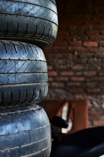 Close-up of tire stack against brick wall