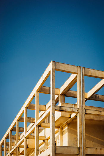 Low angle view of ladder by building against clear blue sky