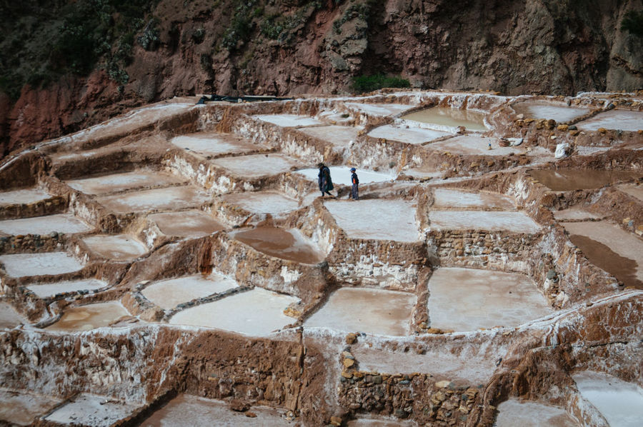 Workers walking down the salt pond terraces in Maras, part of the Sacred Valley of Peru Ancient Beauty In Nature Cusco Day Geometric High Angle View Landscape Mountain Nature Nature Outdoors Peru Sacred Valley Salinas De Maras Salineras De Maras Salt Pans Salt Pans Of Maras Salt Pond South America Terraced Field Two People Urubamba Surreal Surreal Nature