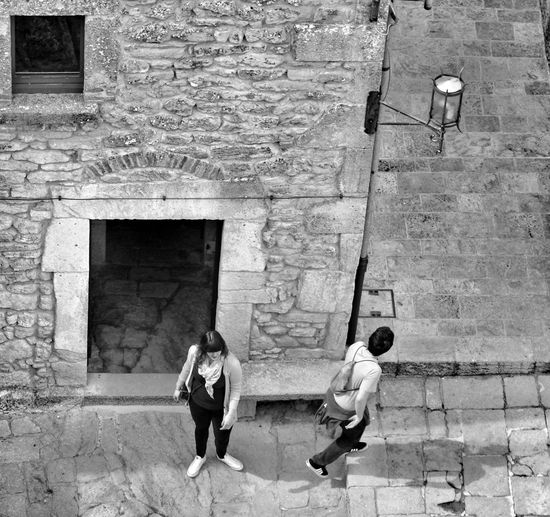 High angle view of two people walking along stone wall