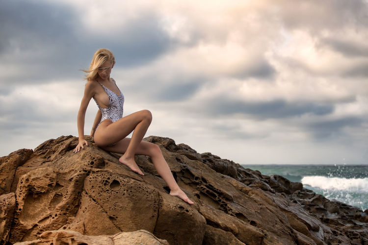 Seductive young woman wearing one piece swimsuit on rocks at beach