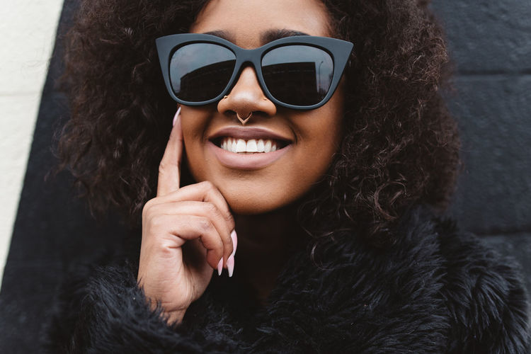 Afro Black Woman Adult Beautiful Woman Clothing Fashion Front View Glasses Hair Hairstyle Happiness Headshot Leisure Activity Lifestyles Natural Hair One Person Portrait Real People Smiling Sunglasses Warm Clothing Women Young Adult Young Women